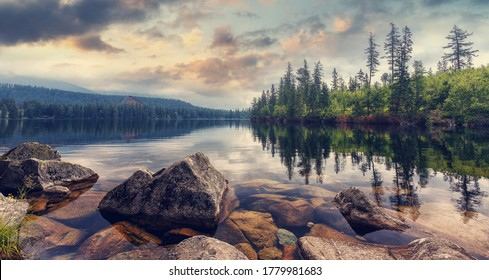 Wild Mountain lake in National Park High Tatra. Dramatic overcrast sky. Strbske pleso, Slovakia, Europe. Beauty world. Wonderful nature landscape of Slovakia during sunset.
