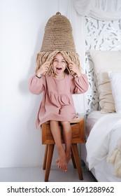 Wildes, unscharfes kleines Mädchen in einem kurzen rosa Kleid, das auf einem Nachttisch sitzt und Lampenschirm als Hut trägt. Ihre Zunge streckte sich aus.