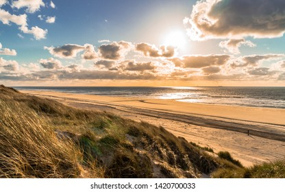 Wild North Sea coastal sunset seascape with wide sandy coastline and tall grass leaning and blown with a strong onshore wind and dramatic cloudy blue sky on Vlieland island in the Netherlands
