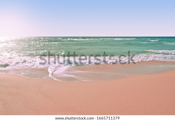 Wild pink sand beach in western  Crimea. Turquoise sea water and clear sky with bright sun backdrop. Summer wallpaper.