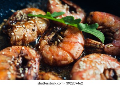 Wild red Argentine shrimp fried in the pan in butter with garlic and sesame seeds, top view