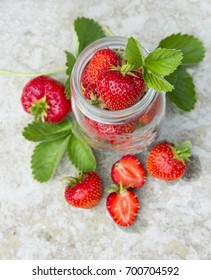 wild red strawberry with green leaf and white flower on the concrete buckground