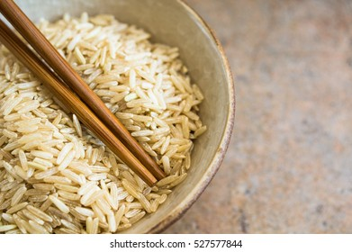 wild rice in ceramic bowl and chopsticks on wooden background