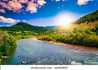 wild river flowing between green mountains on a clear summer day
