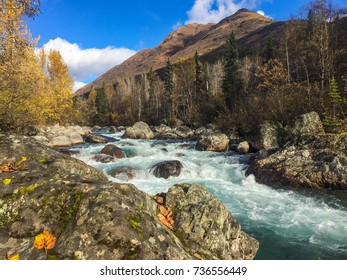 A wild river flows through a rocky landscape in late fall.