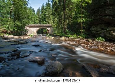 Wild river with old bridge at Zemska Brana, Orlicke mountains, Czech republic - Shutterstock ID 1706133649