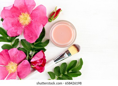 Wild rose extract botanical beauty treatment. Aromatic fresh pink flowers, jar of  natural facial spa product - skincare mask, top view white wooden table