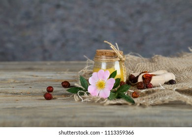 Wild rose hip honey in a glass bottle on a wooden surface. Closeup