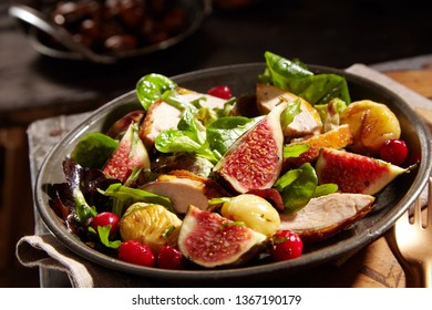 Wild salad with roasted sweet chestnuts, pheasant breast and ripe juicy figs served with basil, baby spinach and berries as a gourmet accompaniment to dinner
