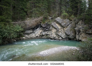 Wild scenery of a river bend with blue green water and washed out riverbanks in a coniferous forest in the Austrian Alps.