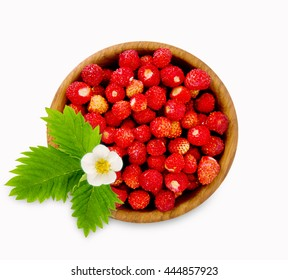 Wild small strawberry in a wooden bowl. Ripe and tasty strawberry isolated on white background. Sweet and juicy berry. Berry useful for strengthening the immune system. Top view.