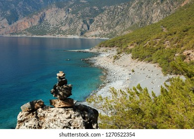Wild and solitary beach with a cairn and the white mountains (Lefka Ori). Photo taken on a seaside coastal path with the Agios Pavlos beach between Agia Roumeli and Loutro in Crete island (Greece)