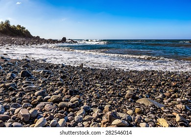 Wild stone beach on shore of the Atlantic ocean with waves and sky with clouds and skyline or horizon in Tenerife Canary island, Spain at spring or summer