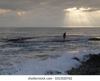 Wild tropical beach with silhouette of a fisherman standing in the sea for traditional fishing on the south coast of Sri Lanka, Indian Ocean, Ceylon, Asia