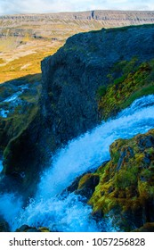 Wild waterfall in the West Fjords of Iceland, view from the top of a waterfall with mountain scenery, Dynjandi