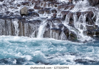 Wild waters (blue) and waterfall cascading over brown rocks, Hraunfossar, Iceland