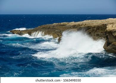 Wild waves of the ocean splash the dry shores of Gozo, Malta