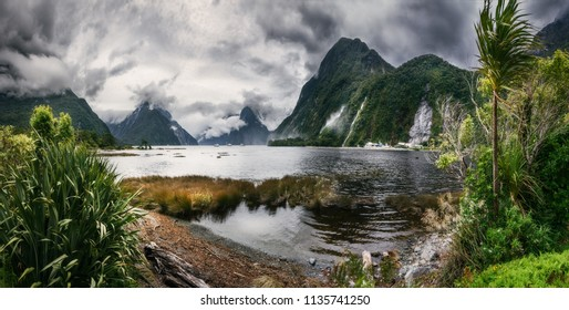 Wild weather conditions at Milford Sound with the clouds engulfing the mountain peaks at Freshwater Basin at the fjord's entry, with Bowen falls and Mitre Peak in Fiordland National Park, New Zealand.