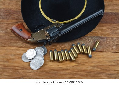 Wild West background - .44 smith and wesson single action revolver gun with cartridges and black hat with silver dollar coins on wooden background