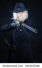 wild west blonde girl wearing black hat with rifle on black background