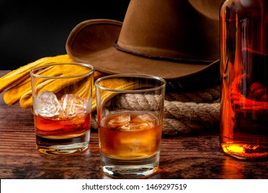 The Wild West concept theme with cowboy hat, rope lasso, leather gloves, two glasses of whiskey on the rocks and bottle of bourbon on wooden table in a vintage saloon against black background