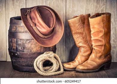 Wild West retro leather cowboy hat, old boots and oak barrel. Vintage style filtered photo