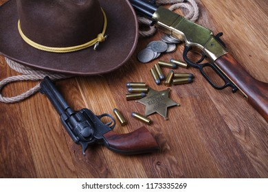 Wild west rifle, ammunition and sheriff badge on wooden table