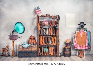 Wild West still life. Retro leather boots, hats, clothes, holsters, USA flag, old gramophone, barrel and poster blank on a wall. Cowboy store interior conceptual design. Vintage style filtered photo - Shutterstock ID 1777728305