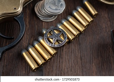 Wild west weapons, ammunition and Texas Rangers star badge with silver dollars on wooden table