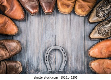 Wild West wooden background concept with retro leather cowboy boots and the horseshoe. Vintage style filtered photo