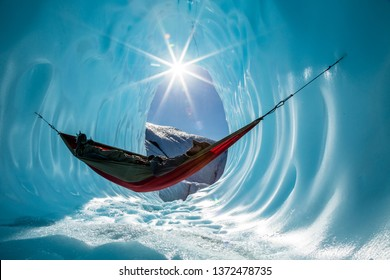 In the wilderness of Alaska, an ice climber has set up a hammock to rest inside of an ice cave on the Matanuska Glacier. The sun peeks in from above the circular blue cavern.