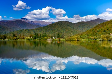 Wilderness Lake Reflections, autumn trees, hills and clouds reflected in the calm blue water of the Lopota lake, Kakheti region, Georgia