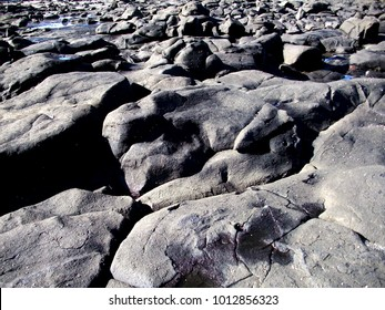 Wilderness of rocks.  Black basalt coastal rocks piled in rough abstract patterns give a feeling of desolation.  Copy space.
