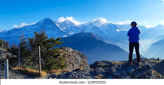 Wilderswill / Switzerland - 11 17 2018: young man standing on the rock and looking to horizon with 3 famous peaks of Swiss Alps mountains (from left Eiger, Monch end Jungfrau), Panorama hike track