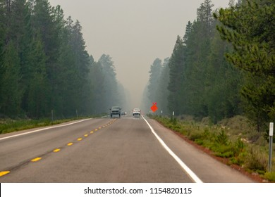 """Wildfire smoke filled highway in Southern Oregon, sign at roadside """"SMOKE LIMITED VISIBILITY""""."""