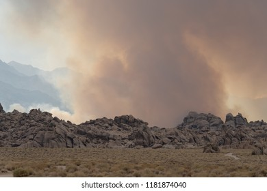 Wildfire starts in the Eastern Sierra Nevada mountains near the Alabama Hills. Dirt road in foreground. Lots of smoke in the air above the rocks. Located in California
