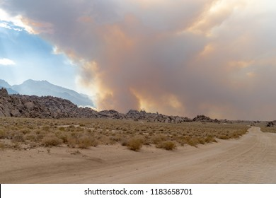Wildfire starts in the Eastern Sierra Nevada mountains near the Alabama Hills. Dirt road in foreground. Lots of smoke in the air. California wildfires