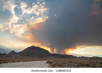 Wildfire starts in the Eastern Sierra Nevada mountains near the Alabama Hills. Dirt road in foreground. Lots of smoke in the air
