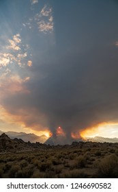 Wildfire starts in the Eastern Sierra Nevada mountains near the Alabama Hills. Dirt road in foreground. Lots of smoke in the air,
