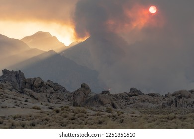 Wildfire starts in the Eastern Sierra Nevada mountains near the Alabama Hills. Dirt road in foreground. Lots of smoke in the air. Sun appears orange