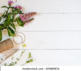 Wildflowers, scissors and thread on white background. Top view