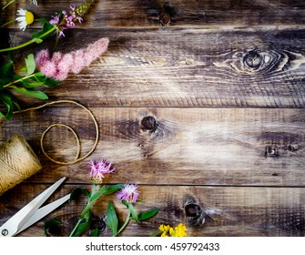 Wildflowers, scissors and thread on a wooden background