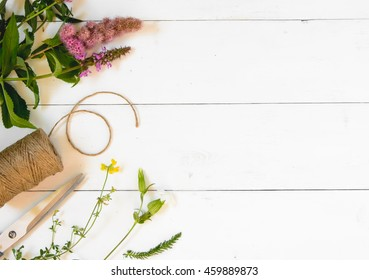 Wildflowers, thread and scissors on a white wooden background. Top view