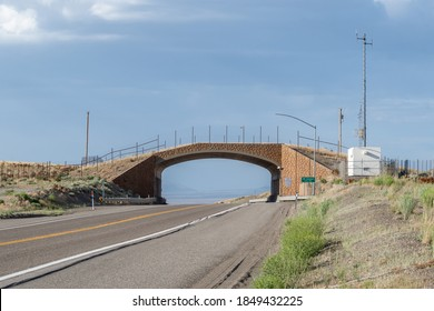 A wildlife crossing overpass along Highway 93 in Elko County, NV allows pronghorn antelope to safely cross the bridge over the road on a grassy strip preventing car accidents.