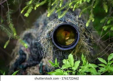Wildlife photographer in the summer ghillie camouflage suit working in the wild