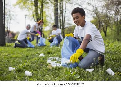 Freiwillige Wildtiere. Energetische männliche Freiwillige mit Mülltüte beim Sammeln von Müll