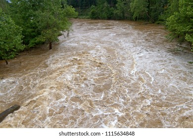 The wildly turbulent, muddy water of a flooding river after days of rain