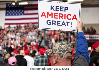 """Wildwood, New Jersey - January 28, 2020: Man holds """"KEEP AMERICA GREAT"""" sign overhead at President Donald Trump's campaign rally held at the Wildwoods Convention Center."""