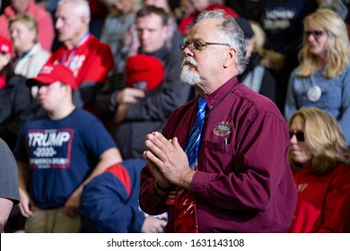 """Wildwood, New Jersey - January 28, 2020: Man holds hands together in prayer during opening ceremonies at President Donald Trump's """"Keep America Great"""" rally held at the Wildwoods Convention Center."""