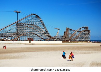 Wildwood, NJ, USA August 25, 2013 A family trudges their beach furniture back from the shore , past a large wooden roller coaster, in Wildwood, New Jersey